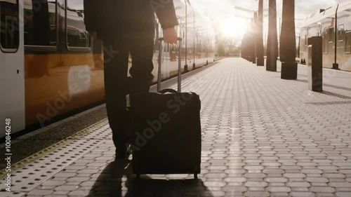 Confident Man With Luggage Walking on Railway Station at Sunset Time. Shot on RED Cinema Camera.