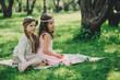 Obrazy na płótnie, fototapety, zdjęcia, fotoobrazy drukowane : happy little girlfriends playing together in spring park. Dressy sisters having fun outdoor on the warm cozy walk. Friendship concept.