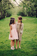 Obrazy na płótnie, fototapety, zdjęcia, fotoobrazy drukowane : two happy dressy little girlfriends hugs outdoor in spring garden. Kid sisters spending time together on the walk