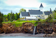 Nova Scotia late spring overcast afternoon.   Rural church in Margarettsville on eastern coast in Canada.  Waterfalls from inland streams spill over a cliff directly into the Atlantic ocean.