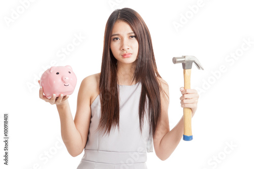 Poster Unhappy  young Asian woman with piggy bank and hammer