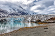 Alaska glacier landscape with reflections in a blue lake of melted water. Climate change impact