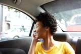 Fototapety Happy african woman in a car talking on cellphone