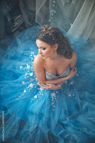 Plakat Beautiful young woman in gorgeous blue long dress like Cinderella with perfect m