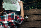 stylish hipster traveler exploring map at sunny forest and lake