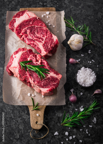 Poster Two raw fresh marbled meat black angus steak ribeye, garlic, salt and  on dark b