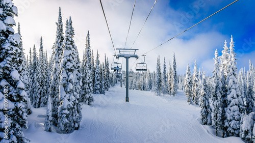 Papiers peints Canada Alpine ski lift and snow covered pistes and trees on a cold winter day under beautiful sky on Mount Morrisey at the village of Sun Peaks in the Shuswap Highlands of central British Columbia