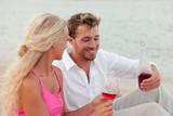 Happy young couple having red wine outdoors on beach. Smiling man and woman in love are holding bottle and wineglasses. Loving male and female are in casual clothing.