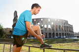 Young male jogger running tying shoelace against Colosseum. Side view of runner preparing for workout on sunny day. Athletic man is in sportswear.
