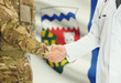 Military man in uniform and doctor shaking hands with Canadian provincies and territories flags on background - Northwest Territories