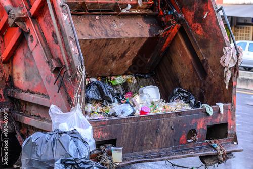 Garbage truck keeping garbage on urban street.