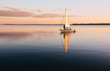 Sailing boat on a calm lake with reflection in the water. Serene scene landscape.