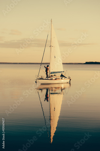 Fototapeta Sailing boat on a calm lake with reflection in the water. Serene scene landscape.