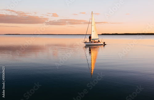 Sailing boat on a calm lake with reflection in the water Poster