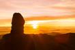 Man standing on a ledge of a mountain, enjoying the beautiful sunset.