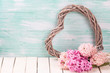 Postcard with pink  hyacinths  and  decorative heart on white  wooden  background against turquoise wall. Romantic background. Selective focus. Place for text.
