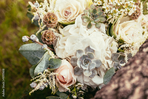 Poster wedding bouquet with roses and succulents on green grass and woo