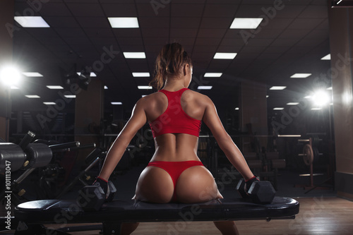 sexy young girl resting after dumbbells exercises