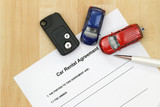 Car rental agreement, remote car key, a pen and mini car models