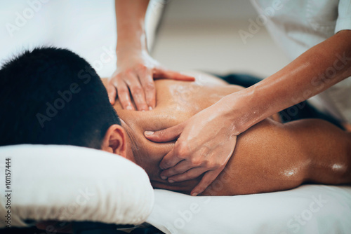 Sports massage. Therapist massaging shoulders Plakát