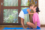 Happy mom and little girl doing yoga exercise on terrace outdoors