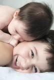 Niño jugando con su hermano bebé con un gesto de felicidad en sus caras