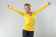 success concept - sexy 20s blond woman with yellow shirt smiling with arms opened for joy or vitality,studio shot