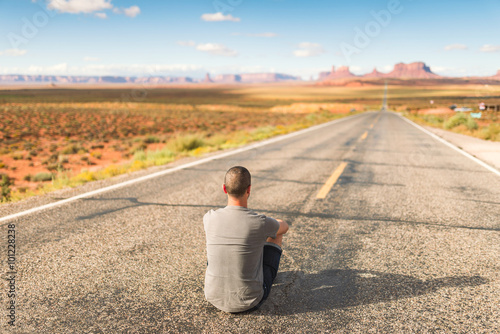 Poster Young man enjoying in Monument Valley, Forrest Gump point.