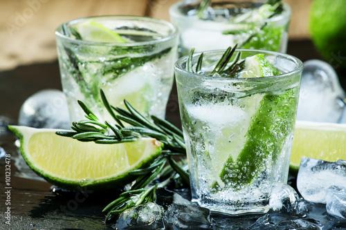 Fototapeta Lime Lemonade with rosemary and ice, dark toned image, selective