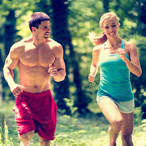 Naklejka Cheerful couple jogging in the park
