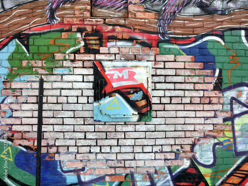 Colorful brick wall with scraps of paint and graffiti - landscape photo Poster