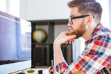Concentrated man in glasses drawing blueprints on computer
