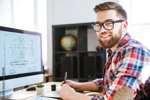Happy designer drawing blueprint on computer using pen tablet Poster