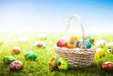Fototapety Unique hand painted Easter eggs in basket and lying on grass, blue sky