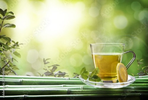 Fototapeta Oriental green tea with mint and lemon on bamboo front