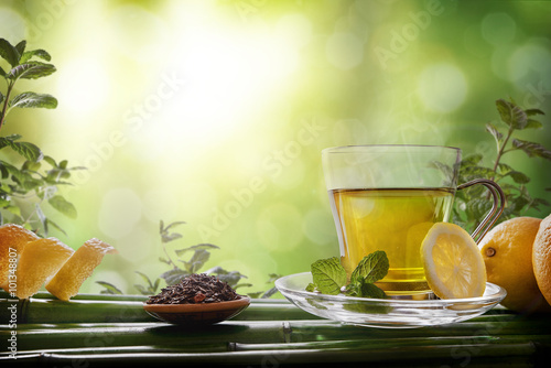 Fototapeta Oriental green tea with mint and lemons on bamboo front
