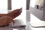 Male hands holding a credit card at a keyboard during online shopping. Shallow D.O.F.