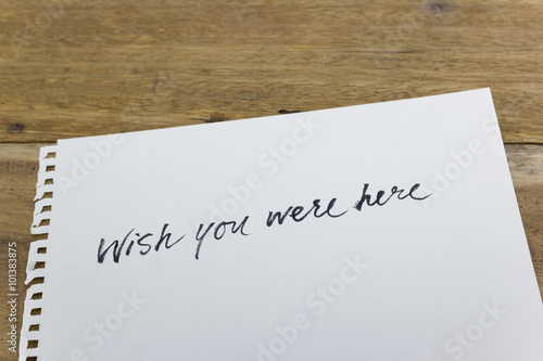"Poster ""wish you were here"" hand written on white paper"