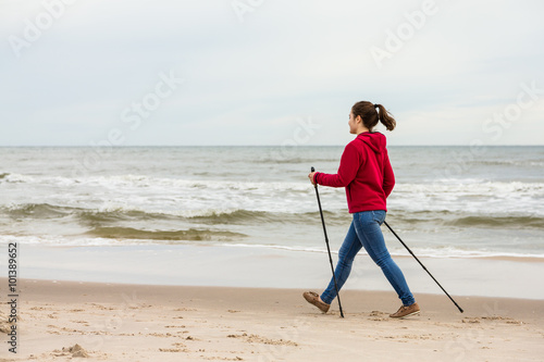Poster Nordic walking - young woman working out on beach