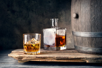Glass of whiskey with ice decanter and barrel