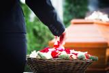 Fototapety Frau auf Beerdigung streut Rosenblätter auf Sarg