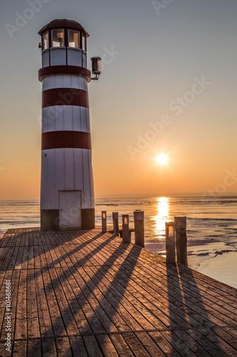 Holzsteg mit Leuchtturm im Winter vor gefrorenem See im Sonnenuntergang - 101468681
