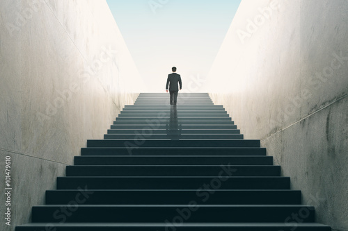 Fototapeta Ambitions concept with businessman climbing stairs