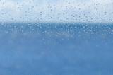 blur blue water and sky through transparent rainy window