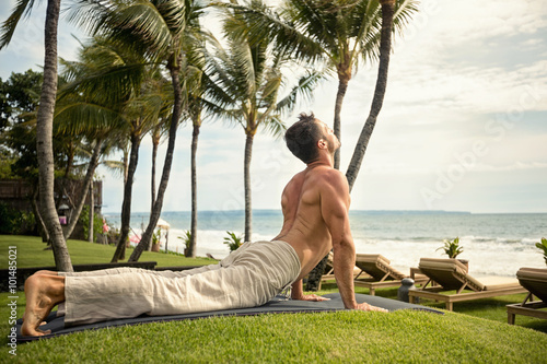 fit young man doing the cobra pose in nature Poster