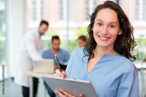 Portrait d'une jeune infirmière attrayante à l'hôpital Poster