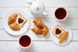 Obrazy na płótnie, fototapety, zdjęcia, fotoobrazy drukowane : Breakfast for couple with toasts, heart shaped jam, croissants, and tea on white wooden table background