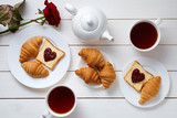 Breakfast for couple on Valentines Day with toasts, heart shaped jam, croissants, red rose flower and tea, white wooden table background.