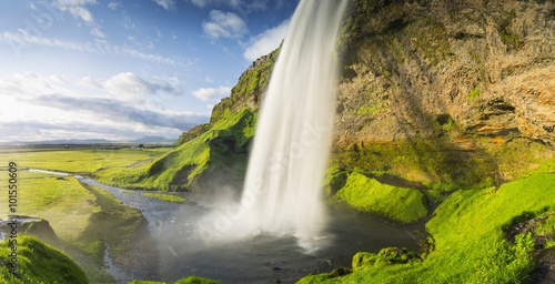 warm sun lights and waterfall with green canyon and blue sky in Iceland