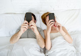young couple using mobile phone in bed ignoring each other in relationship communication problems